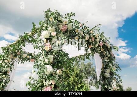 Eine festliche Chuppah mit frischen Blumen für eine Hochzeit im Freien Zeremonie dekoriert. - Stockfoto