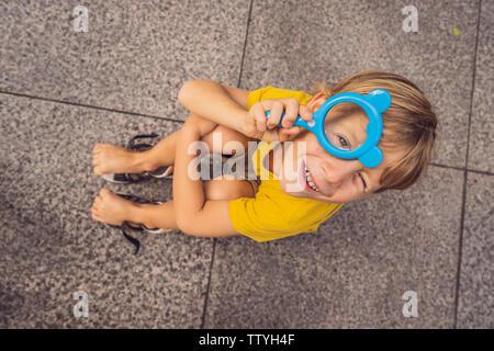 Junge sitzt auf dem Boden und schaut in eine Lupe - Stockfoto