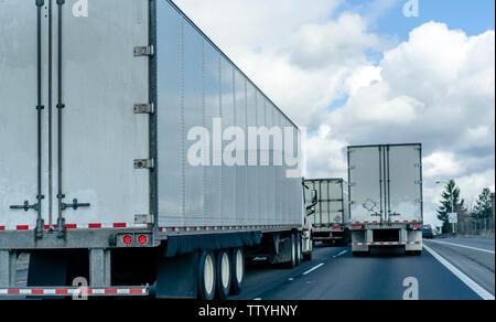 Rückansicht der Konvoi der gewerblichen Güterverkehr von Big Rig halb Lkw mit Auflieger, die auf der breiten Autobahn auf mehrere Zeilen fo - Stockfoto