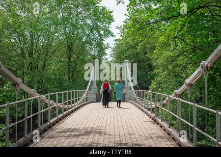Ansicht der Rückseite zwei junge Norwegische Frauen überschreiten die Aamodt Bru Brücke über dem Fluss Akerselva in der Grunerlokka Bezirk von Oslo, Norwegen. - Stockfoto