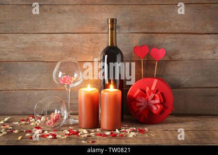 St. Valentines Tag Konzept. Zusammensetzung von Wein, Rosen, Kerzen und Geschenkbox auf hölzernen Tisch - Stockfoto