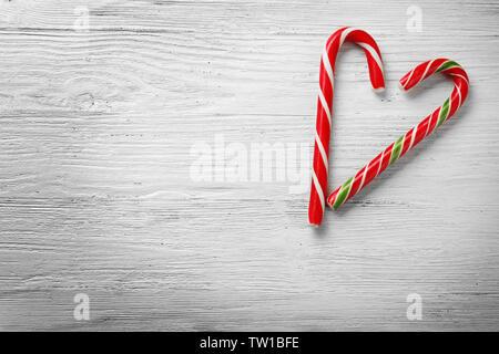 Herzform mit Weihnachten Candy canes gemacht auf hölzernen Hintergrund - Stockfoto