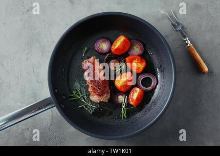 Lecker Steak mit aromatischem Rosmarin, Tomaten und Zwiebel in der Grillpfanne auf grau Tabelle - Stockfoto