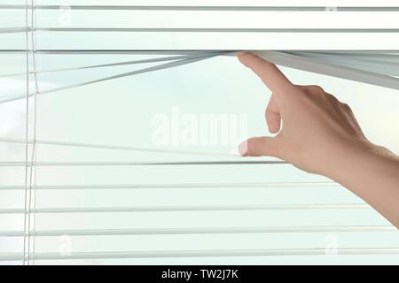 Weibliche Hand trennen Lamellen von Jalousien durch die Fenster sehen, - Stockfoto
