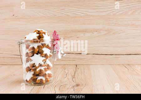Zimtsterne, Zimtsterne, Deutsche Weihnachten Plätzchen in einem Glas mit Weihnachten Dekoration auf braunem Holz- Hintergrund mit viel Platz kopieren. Niedrig - Stockfoto