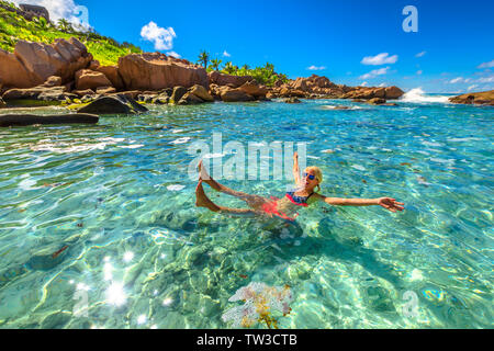 Schwimmbad im Anse Cocos, La Digue. Glückliche Frau im Bikini liegt am türkisblauen Wasser der natürlichen Pool im Anse Cocos Beach durch Felsen geschützt - Stockfoto
