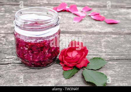 Stau Rosenblätter auf einen hölzernen Tisch. Blume Konfitüre. Gesundes Essen. Platz kopieren - Stockfoto