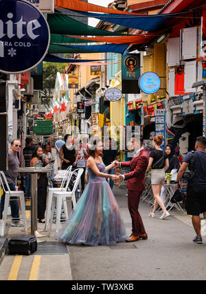 Ein junges Paar in Singapur pose für professionelle Bilder in Haji Lane in bunten Hochzeit Art Outfits von der Öffentlichkeit beobachtet gekleidet. - Stockfoto