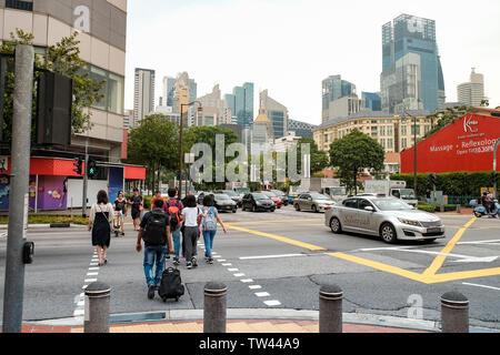 Eine vielbefahrene Straße überqueren mit Fußgänger und Verkehr über South Bridge Road Singapur. - Stockfoto