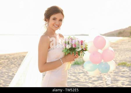 Schöne Braut mit wedding bouquet am Strand - Stockfoto