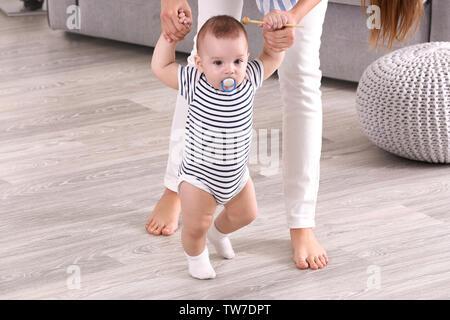 Mutter ihr Baby zu Fuß auf dem Boden zu Hause helfen - Stockfoto
