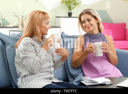 Reife Frau und ihre Tochter Kaffee trinken und reden zu Hause - Stockfoto