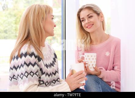 Reife Frau und ihre Tochter Kaffee trinken während der Sitzung auf der Fensterbank - Stockfoto
