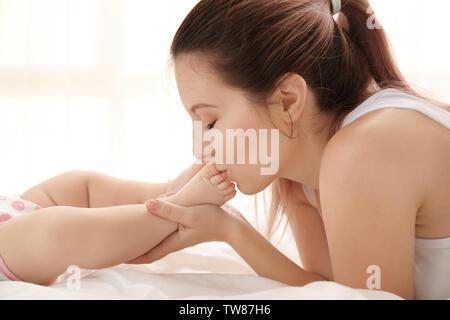 Mutter Füße Ihres Babys zu Hause küssen - Stockfoto