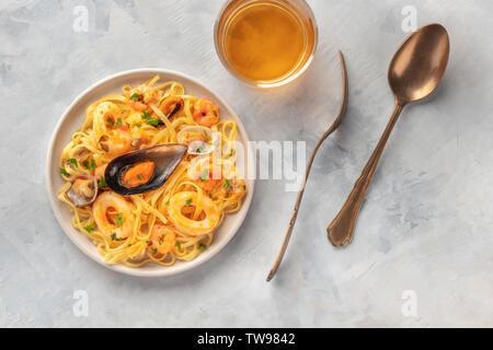 Meeresfrüchte Pasta, Overhead closeup erschossen. Tagliolini mit Muscheln, Garnelen, Muscheln und Tintenfisch Ringe, mit einem Glas Weißwein - Stockfoto