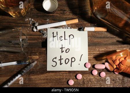 """Beachten Sie, mit den Worten 'Hilfe zu stoppen"""", Alkohol, Drogen und Zigaretten auf dem Tisch - Stockfoto"""