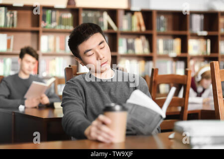 Asiatische student mit Buch studieren in Bibliothek - Stockfoto
