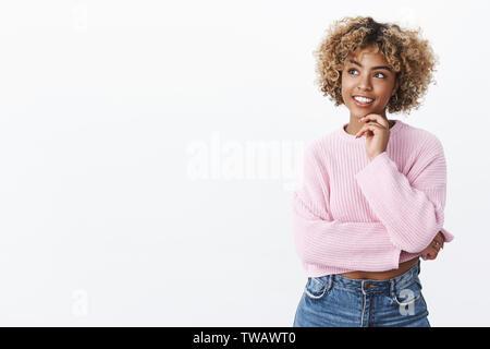 Attraktive junge Afrikaner - amerikanische Studentin mit blonden Haaren die Hand am Kinn und auf der Suche an der oberen linken Ecke erfreut wie Denken, posing Stockfoto