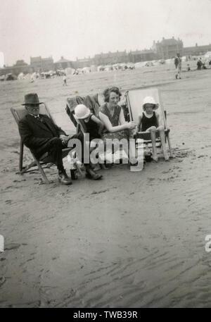 Familie Gruppenfoto am Meer. Ein älteres Paar sitzen auf den Liegestühlen mit zwei Mädchen in die passende Hüte und Badesachen, die Erwachsenen lächelnd, während die Kinder schauen weniger sicher das theyre, das sich zu amüsieren. Der Vater oder Großvater trägt robuste Stiefel und hat eine Flasche trinken unter seinem Liegestuhl! Datum: ca. 1920 s Stockfoto