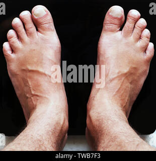 Nahaufnahme der männlichen Füße auf Schwarz digital Stock Glasmaßstäbe. Ernährung und Körpergewicht. Von oben nach unten anzeigen. Sport und Lifestyle Konzept. Mann, der auf der Skala. - Stockfoto