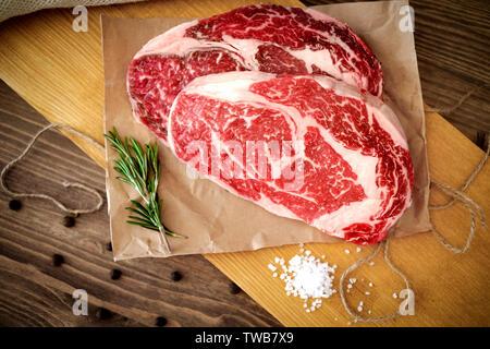 Zwei Rohmaterial Rib Eye Steak auf einem Holzbrett auf einen Tisch für den Grill vorbereitet. Ansicht von oben rustikalen Stil - Stockfoto