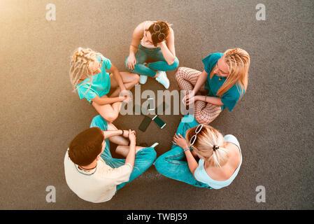 Die Jugendlichen sitzen auf dem Boden mit Mobiltelefonen im Kreis - Stockfoto