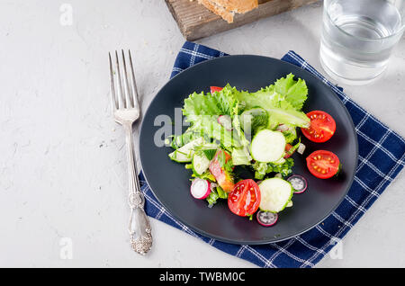 Salat von frischem Salat, Tomaten, Gurken, Rettich, grünen und Zwiebeln für das Mittagessen auf dem Tisch. Gesunde Ernährung Konzept. Platz kopieren - Stockfoto
