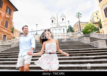 Happy romantisches Paar, Hände auf der Spanischen Treppe in Rom, Italien. Freudige junge interracial Paare gehen auf die Reise Sehenswürdigkeiten touristische Attraktion Symbol während ihrer Romanze Europa Urlaub - Stockfoto
