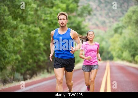 Fitness Laufen junge Paar training Marathon konzentrierte sich auf Road Trail im Sommer Natur konzentriert. Sportlich gesund gemischten Rasse Frau und stattlichen kaukasischen Mann joggen außerhalb. Sportliche Menschen in 20 s - Stockfoto