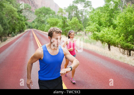 Läufer Training - junge Gemischtrassiges Paar, dass das Training auf der Straße in der wunderschönen Natur konzentriert. Kaukasische fitness Modell mann Kontrolle Zeit oder Impuls auf die Herzfrequenz Monitor anschauen. - Stockfoto