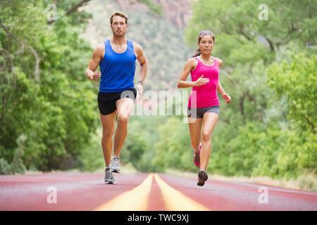 Ausführen von jungen Menschen - zwei Läufer Joggen auf der Straße in der Natur Training für Marathon laufen. Multikulturelle Paare - asiatische gemischten Rennen schönes Modell Frau und Kaukasier Männlich fitness Modell der Ausübung - Stockfoto