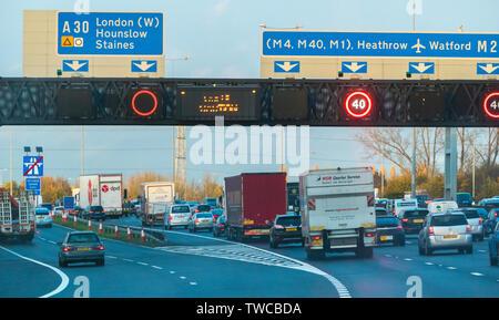 Viel Verkehr auf M25 London Orbital in Middlesex, mit einem 30 Zufahrtsstraße und Overhead Zeichen zeigen, M4, M40 und M1 Autobahnen in der Nähe. England, UK. - Stockfoto