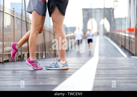 Küssen Paar läuft - Liebe sport romantischen dating Konzept. Nahaufnahme von Laufschuhen und Mädchen stehen auf Zehen Freund beim Joggen Workout Training auf der Brooklyn Bridge, New York City, USA zu küssen. Stockfoto