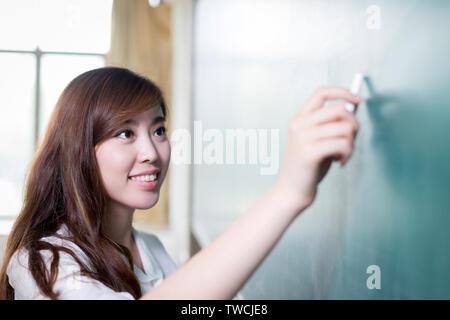 Asiatische schöne Frau schreiben auf blackboard - Stockfoto