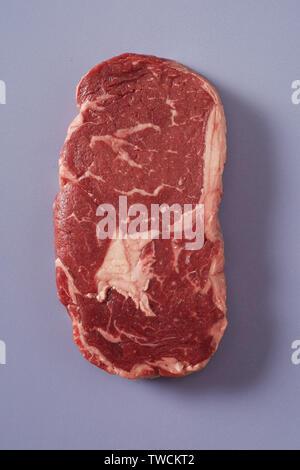 Dicke saftige raw marmoriert Rib Eye Rindersteak auf Blau Grau gesehen von Overhead bereit für das Kochen an einem sommerlichen Picknick oder BBQ - Stockfoto