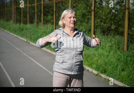 Gealterte Frau Übungen im öffentlichen Stadion. - Stockfoto
