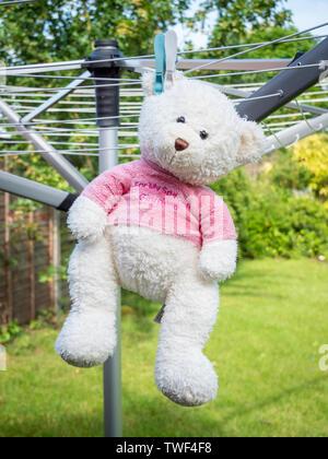 Ein Weißer Teddybär hängend auf einer Wäscheleine zum Trocknen nach dem Waschen - Stockfoto