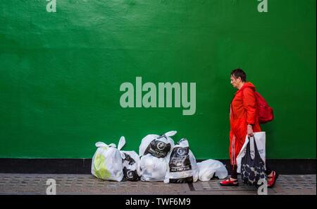 Frau in orange Regenmantel wandern mit Taschen shopping Vergangenheit grün gestrichenen Wand mit Säcke Müll vor der Wand in Central London. - Stockfoto