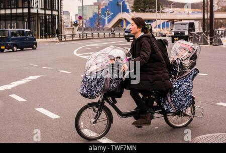 Frau Reiten Fahrrad mit Kleinkind Sitze an der Vorder- und Rückseite des Fahrrads in Asakusa Tokyo in Japan. - Stockfoto