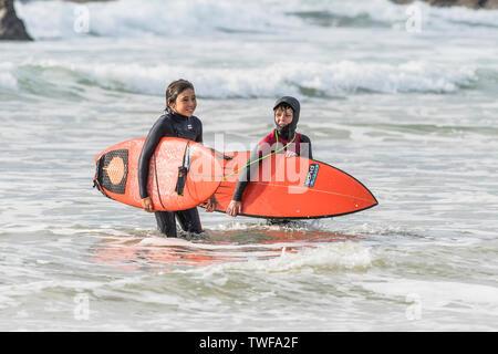 Zwei junge Surfer mit ihren roten Skinpups Surfbretter und zu Fuß aus dem Meer auf den Fistral Beach in Newquay in Cornwall. - Stockfoto