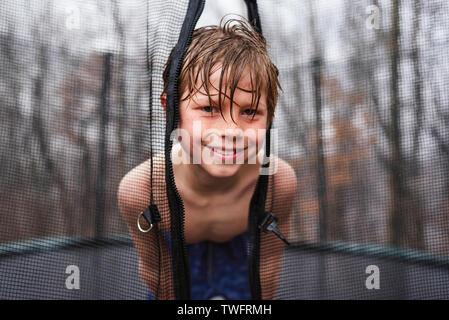 Portrait von Kind nass und glücklich spielen auf einem Trampolin im Regen - Stockfoto