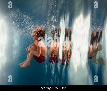 Junge in einen Pool springen - Stockfoto