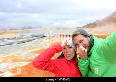 Island lustige Touristen paar Spaß unter selfie Foto mit im Landmark Ziel: namafjall Hverarondor mudpot hverir auch als Schlammbad hot spring oder fumarole. Geruch von Schwefel auf Vulkan - Stockfoto