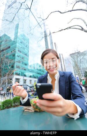 Junge Geschäftsfrau auf dem Smartphone Essen Salat auf Mittagspause im City Park Leben gesunder Lebensstil arbeiten an Smart Phone. Happy multirassischen Geschäftsfrau, Bryant Park, Manhattan, New York City, USA - Stockfoto