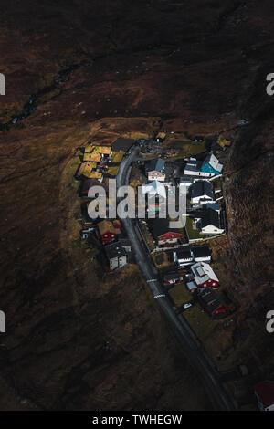 Färöischen Dorf von oben gesehen bei einem Hubschrauberflug über die Moody Frühling Landschaft der Färöer (Färöer, Dänemark, Europa) - Stockfoto
