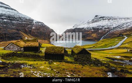 Panorama Blick auf typisch Färöischen, mit Gras bewachsene Kabinen in dem kleinen Dorf Saksun während der frühen Frühling mit schneebedeckten Bergen (Färöer Inseln) - Stockfoto