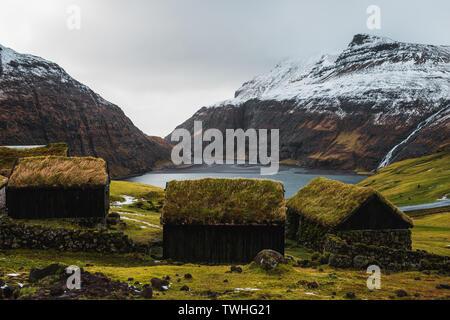 Typisch Färöischen, mit Gras bewachsene Kabinen in dem kleinen Dorf Saksun während der frühen Frühling mit schneebedeckten Bergen und tiefblauen Meer (Färöer Inseln) - Stockfoto