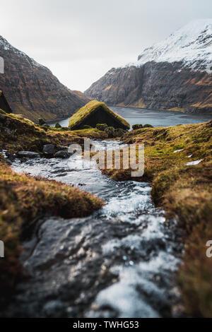 Typisch Färöischen, mit Gras bewachsene Kabinen in dem kleinen Dorf Saksun während der frühen Frühling mit schneebedeckten Bergen und einem kleinen Fluss (Färöer Inseln) - Stockfoto