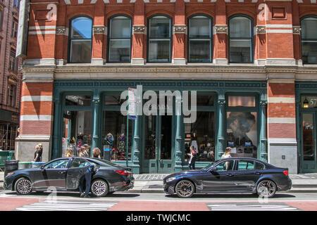 New York, 6/15/2019: Zwei Fahrzeuge sind vor einer Prada Stores in SoHo geparkt. - Stockfoto