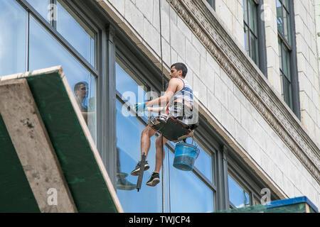 New York, 6/15/2019: Scheibe Fenster, während Sie bei der Arbeit ausgesetzt sein ein Gebäude in SoHo. - Stockfoto